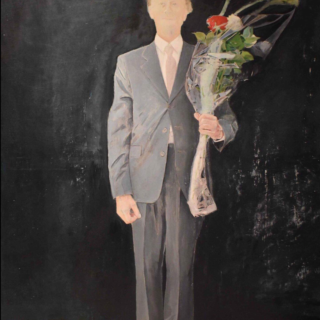 Man against a black backdrop holding a large bunch of flowers