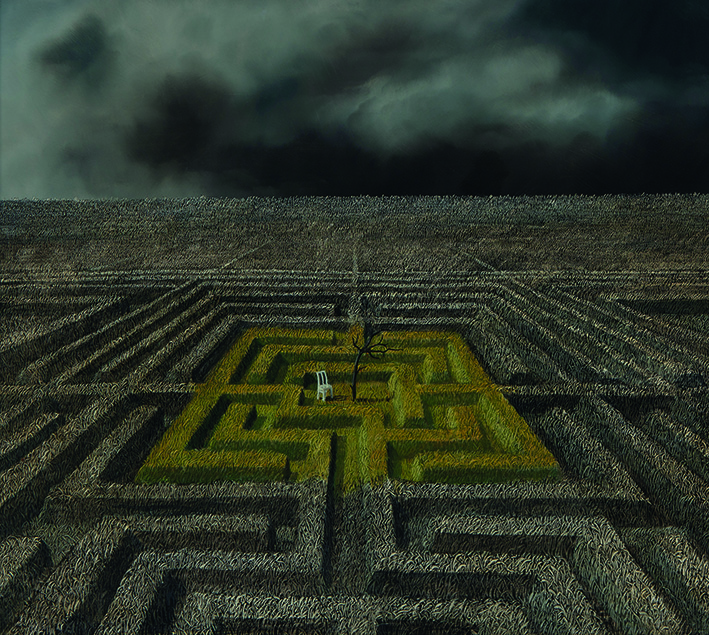 A maze is cut out from a field, with a white chair and bare tree at the centre of the maze