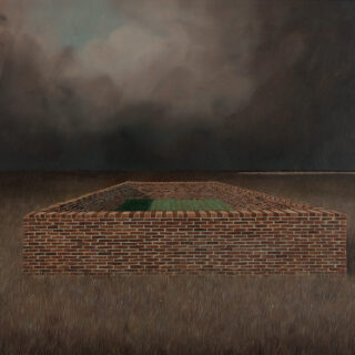 A brick wall surrounds a lush green patch within a larger field under a dark cloudy sky