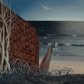 A large brick wall runs down a slope to the sea with bare trees growing in the foreground